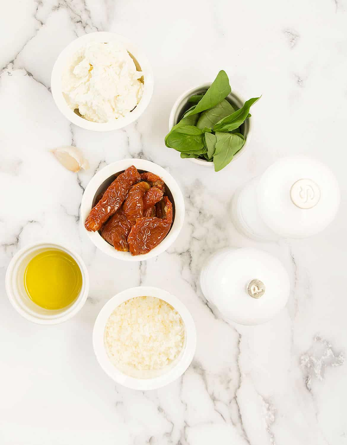 The ingredients for this sun dried tomato pesto are arranged on a white marble surface.