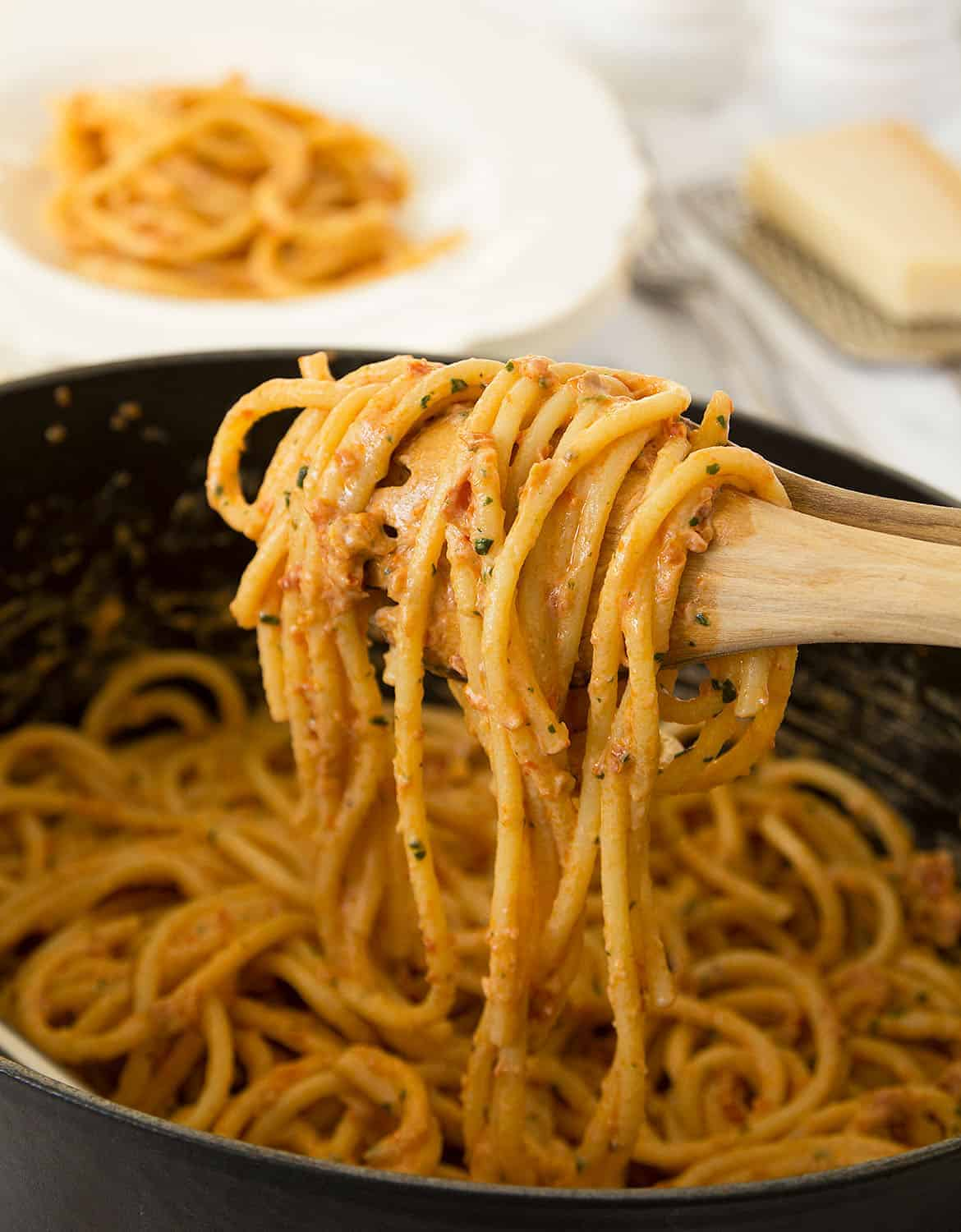 Two wooden spoons are lifting some red pesto spaghetti.