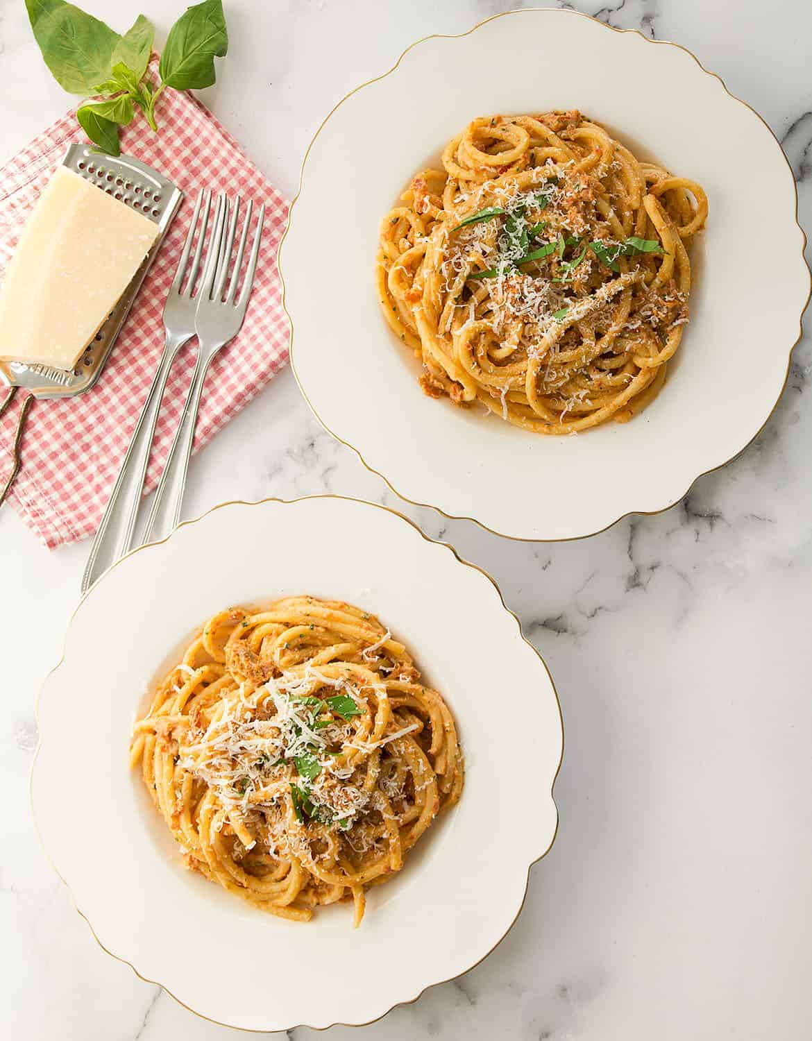 Sun dried tomato pesto pasta served into white plates with freshly grated parmesan.