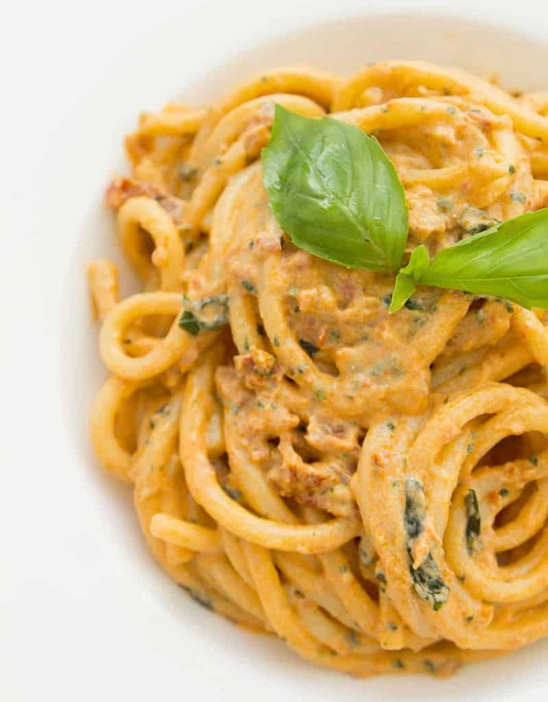 Sun dried tomato pesto spaghetti on a white plate with two basil leaves on top.