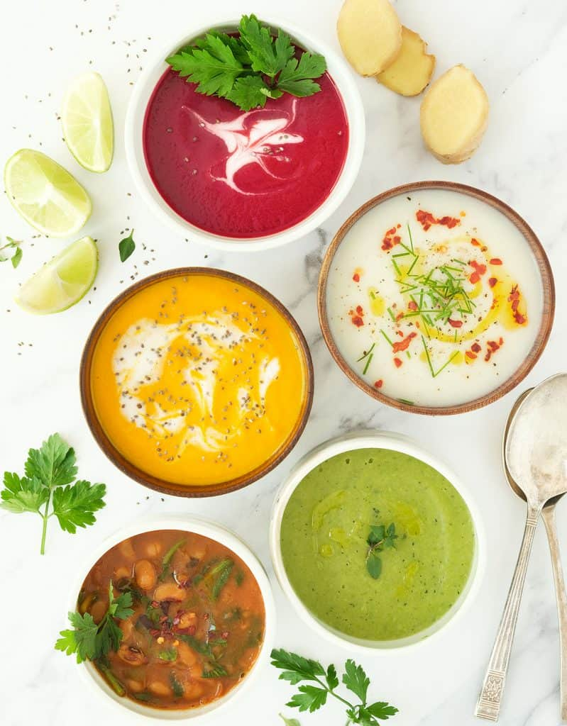 Five bowls of colorful weight loss soups over a white marble background.