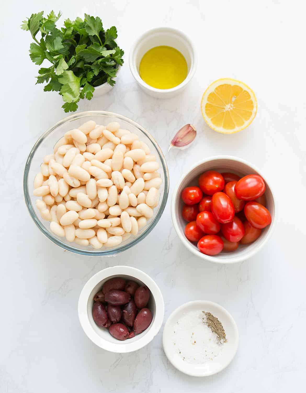 The ingredients for this cannellini bean salad arranged on a white marble surface.