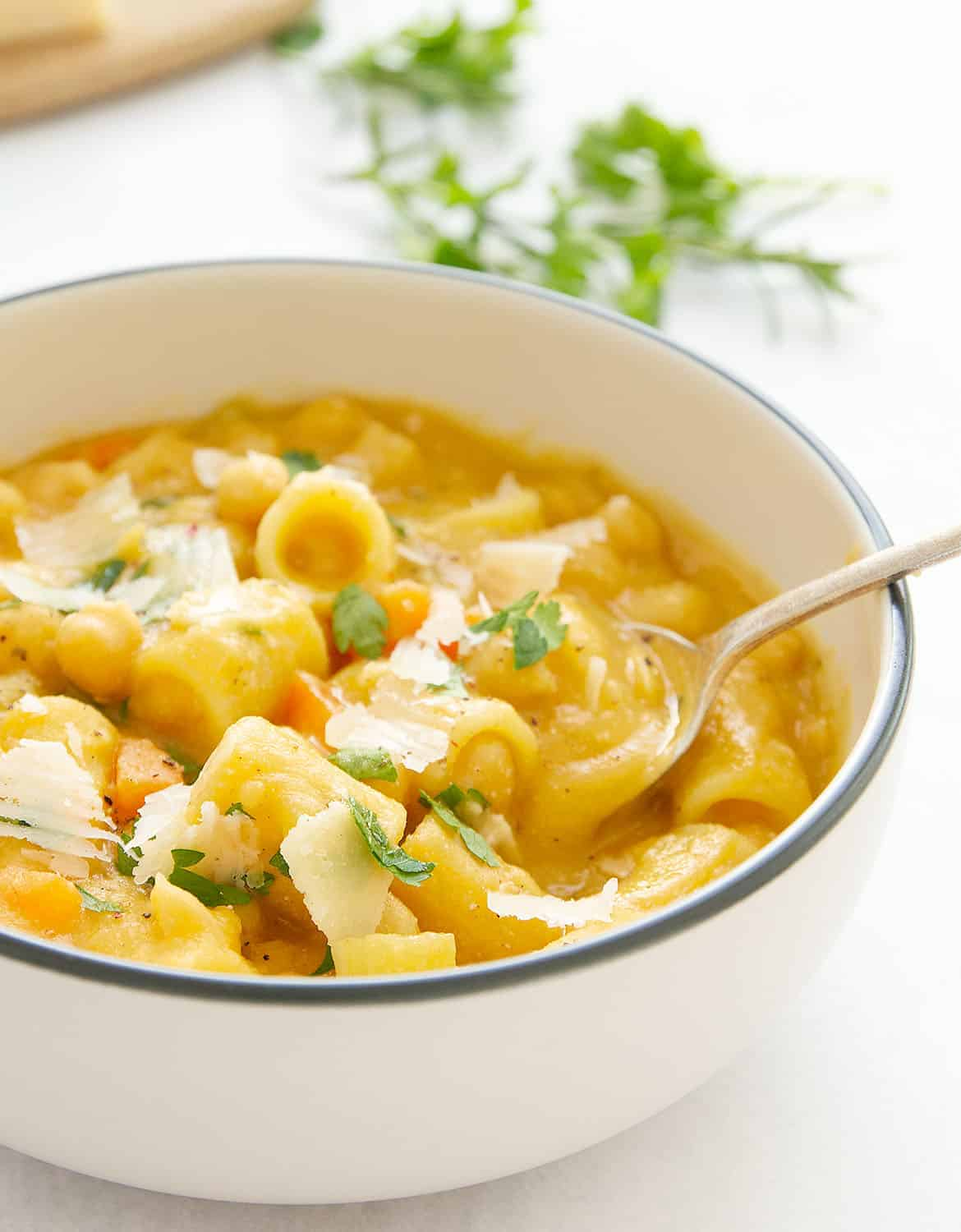 Pasta with chickpeas in a white bowl with a spoon.