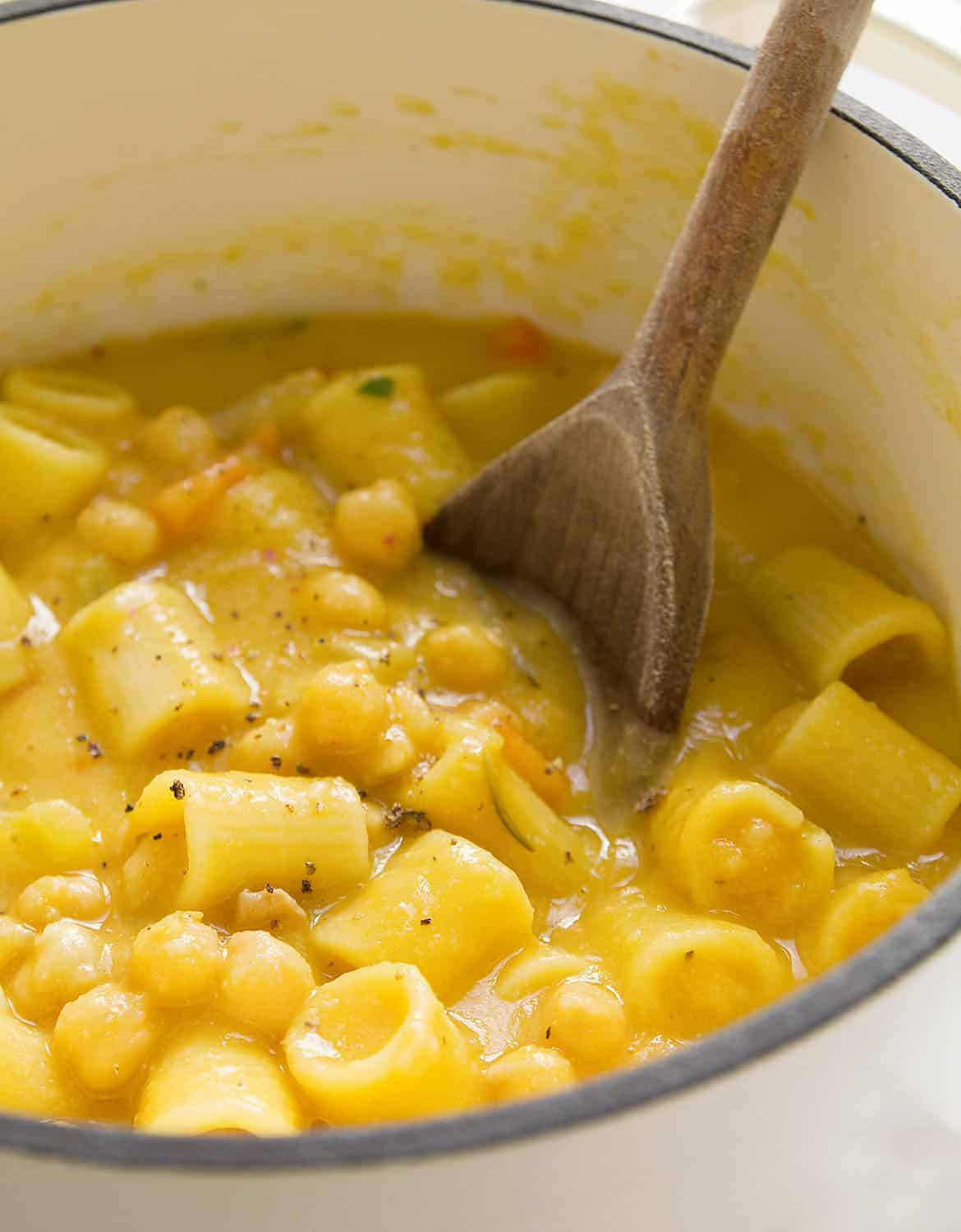 A wooden spoon is stirring pasta with chickpeas in a white pot.