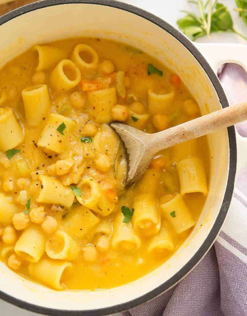 A wooden spoon stirs pasta with chickpeas in a white cast iron pot.