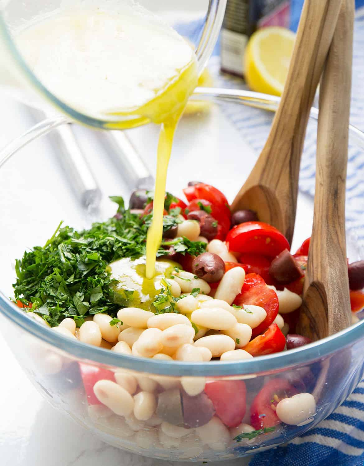 A glass bowl is pouring the lemon dressing into the cannellini bean salad.