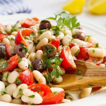Cannellini bean salad on a white plate with a wooden spoon.