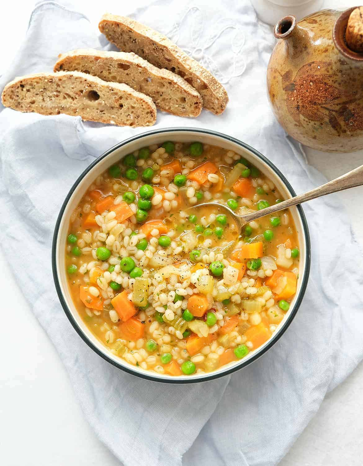 Vegetable barley soup in a white bowl with a spoon. Three slices of bread next to it.