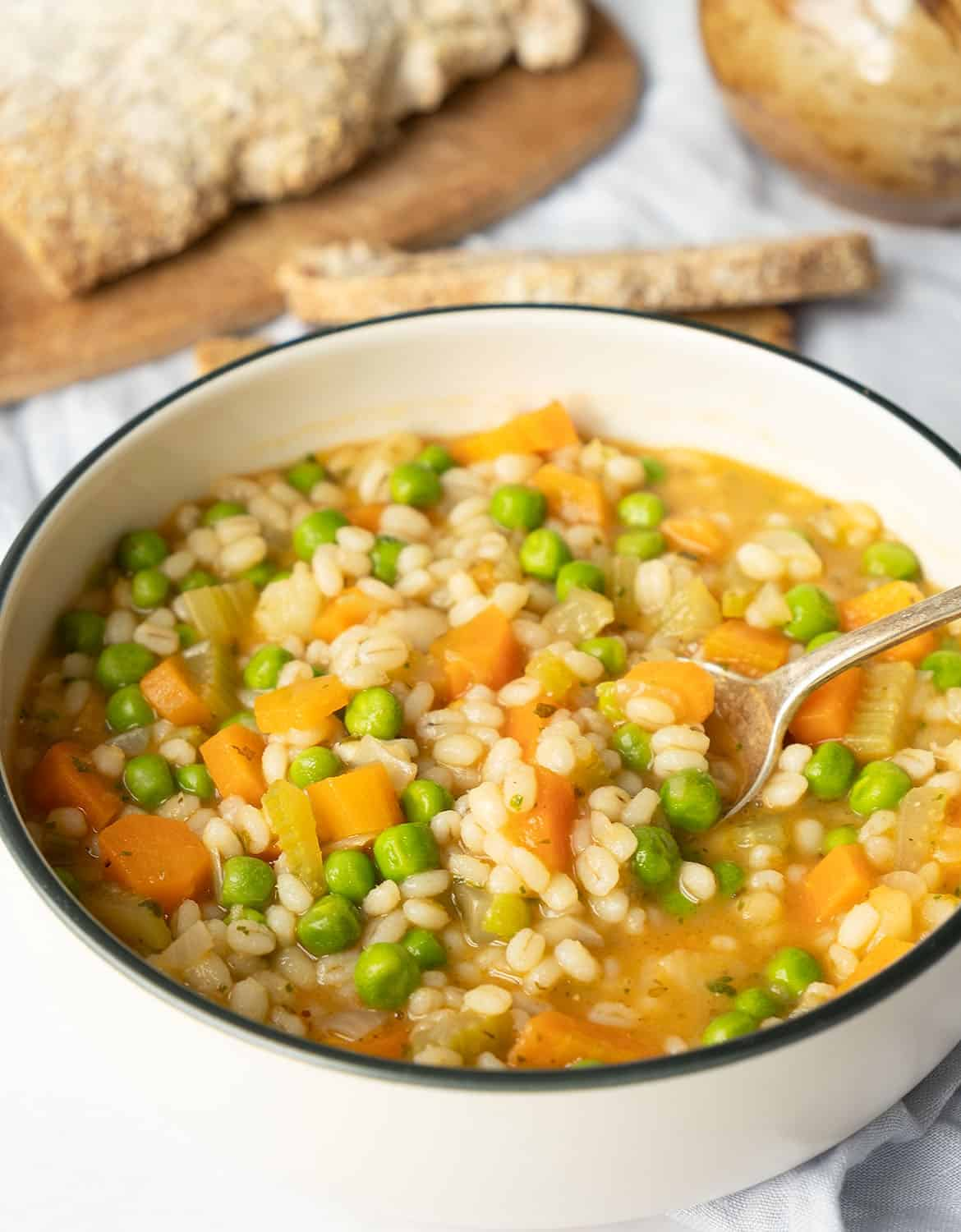 Vegetable barley in a white bowl with a spoon. Bread on the background.