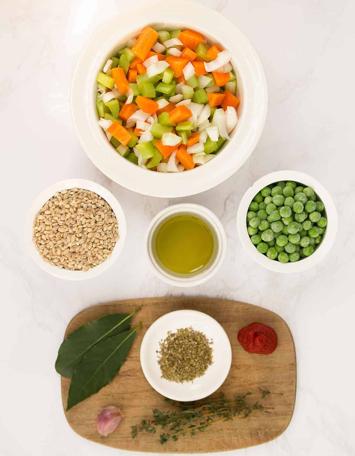 The ingredients to make this barley soup are arranged on a white marble table.
