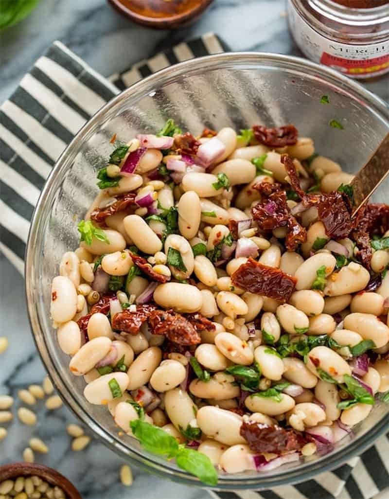A glass serving bowl full of cannellini bean salad with sun dried tomatoes - A Saucy Kitchen