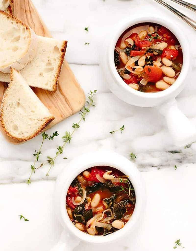 Two small white bowls full of kale white bean stew -  Blissful Basil