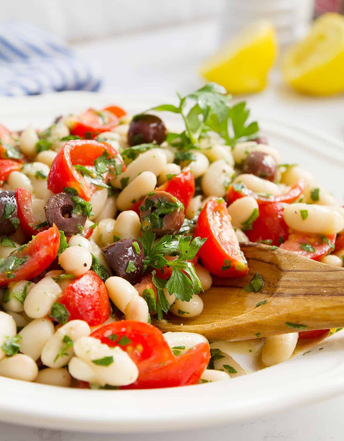 Cannellini bean salad with tomatoes and olives on a white serving plate - The Clever Meal