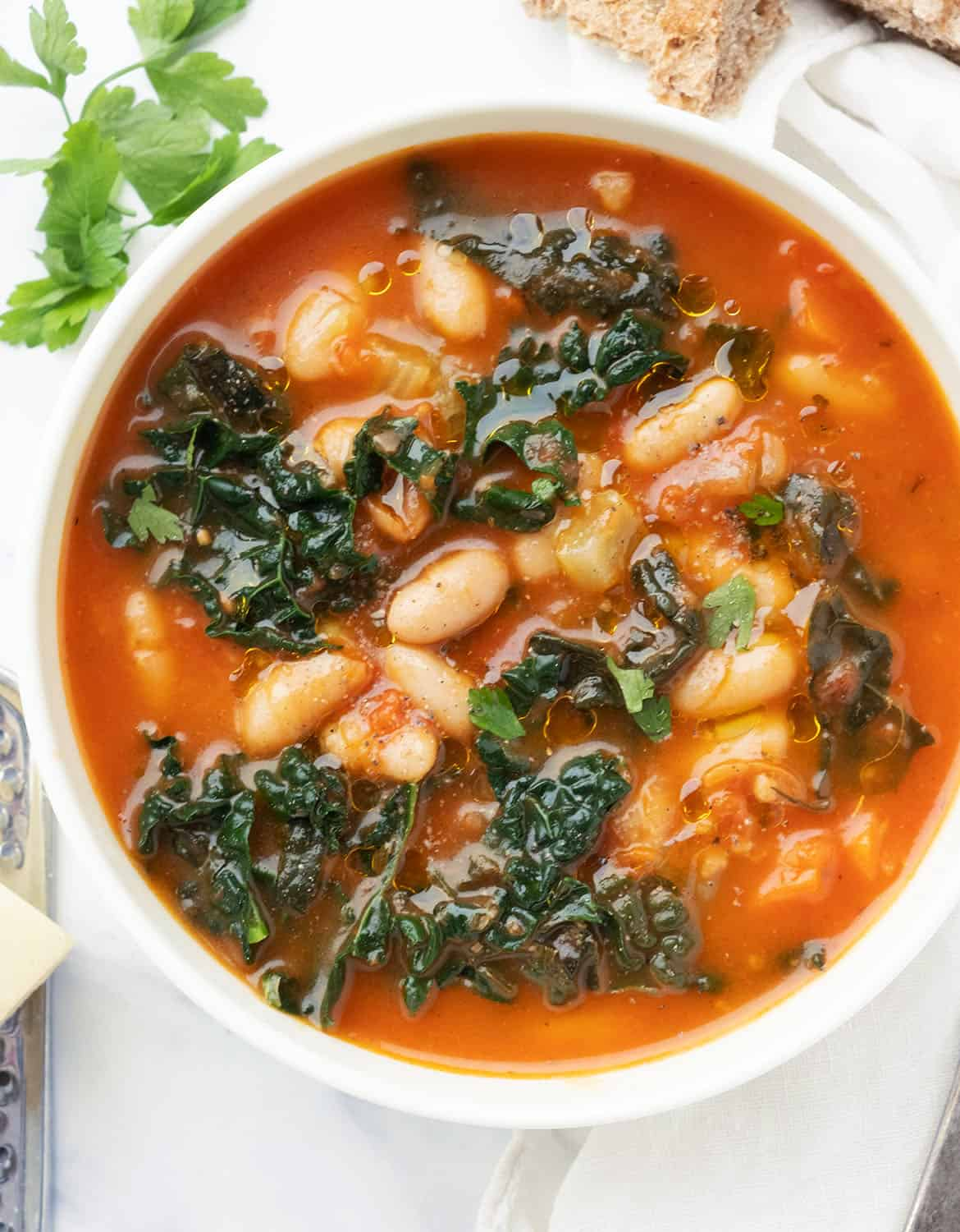 Top view of a bowl of cannellini bean and kale soup over a white background.