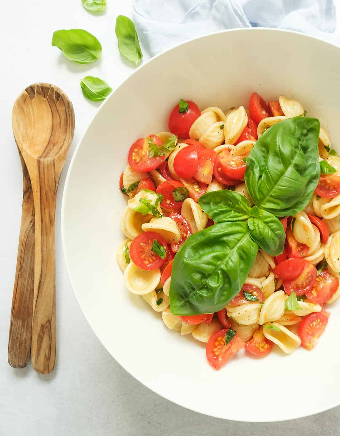 Vegan tomato pasta salad in a white bowl with large basil leaves - The Clever Meal