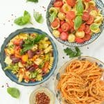 Three plates with different vegan pasta recipes with fresh herbs and chili flakes over a white marble background.