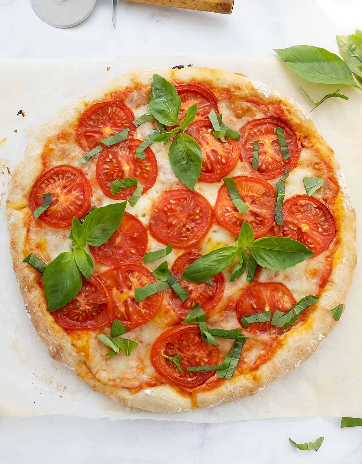 A caprese pizza on a white background with fresh basil leaves.