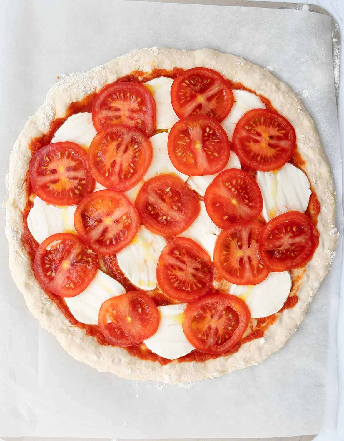 A pizza caprese with slices of tomato and mozzarella before baking.