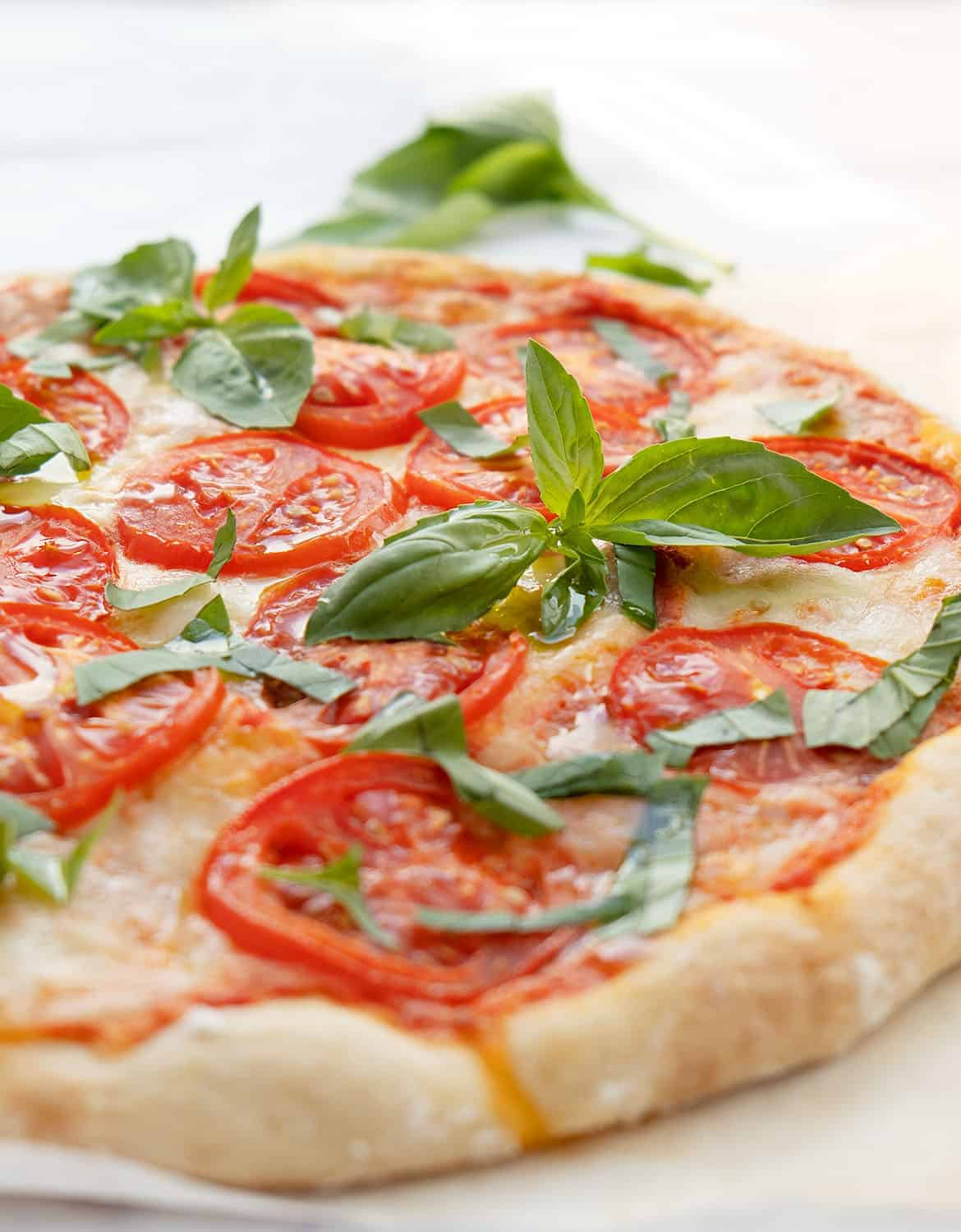 A delicious Caprese pizza on a white plate with green basil leaves.