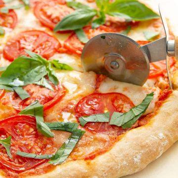 A pizza cutter is cutting a slice of caprese pizza.