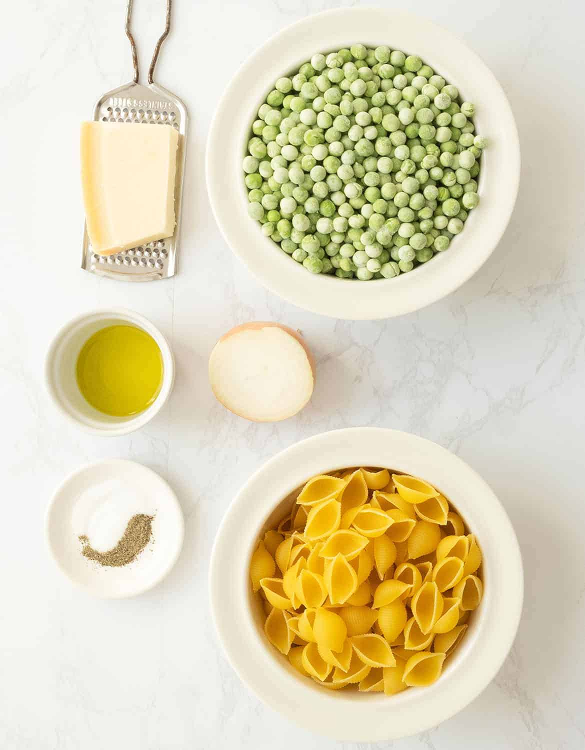 The ingredients to make this pasta with peas are arranged on a white marble table.