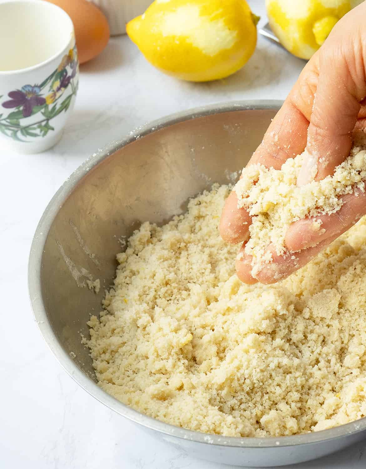 How to make the ricotta cake crumbles: rub flour, egg, sugar, oil and lemon zest.