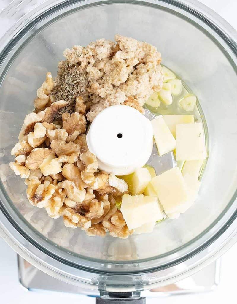 Walnuts, bread, cheese, garlic, olive oil in a food processor bowl.