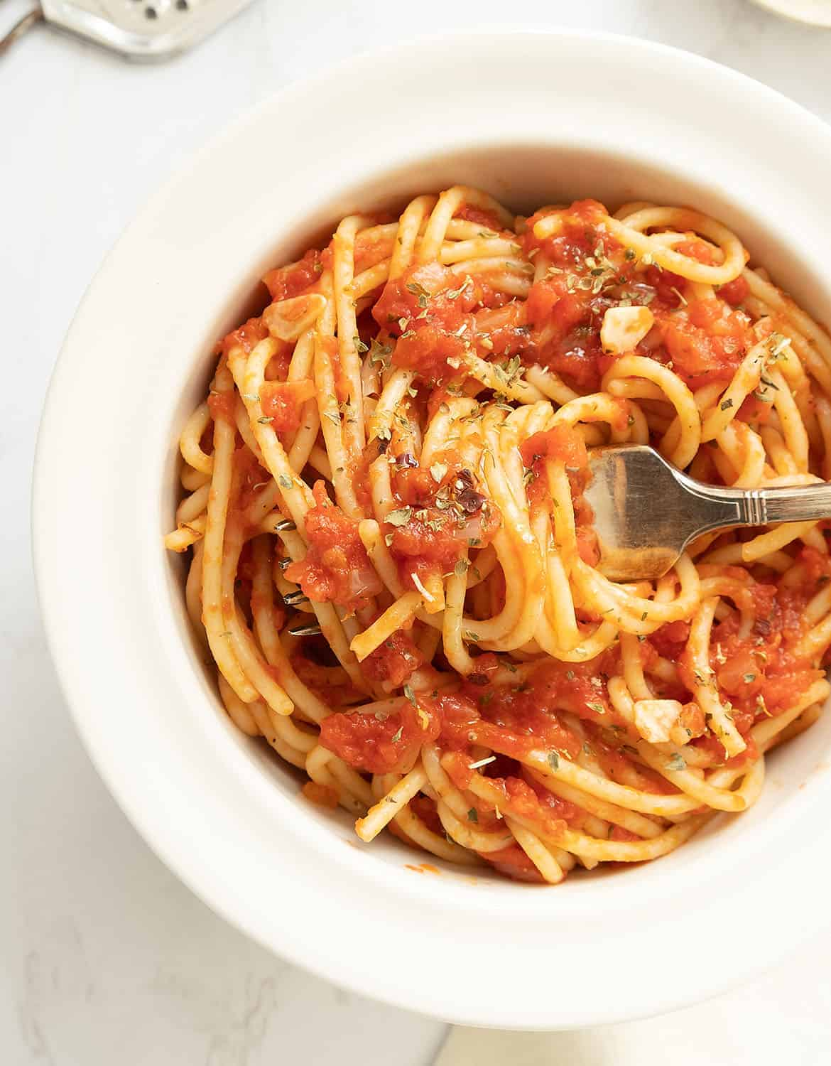 Vegan marinara sauce and spaghetti in a white bowl with a fork - The Clever Meal