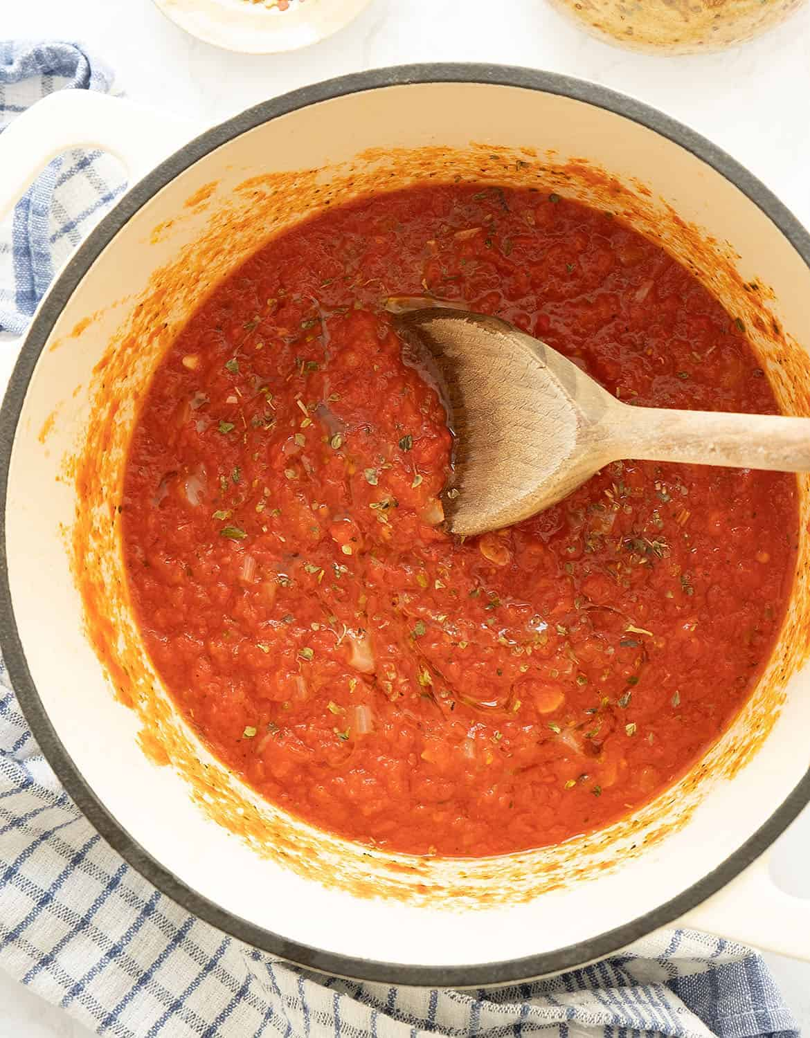Italian marinara sauce in a white casserole with a wooden spoon.