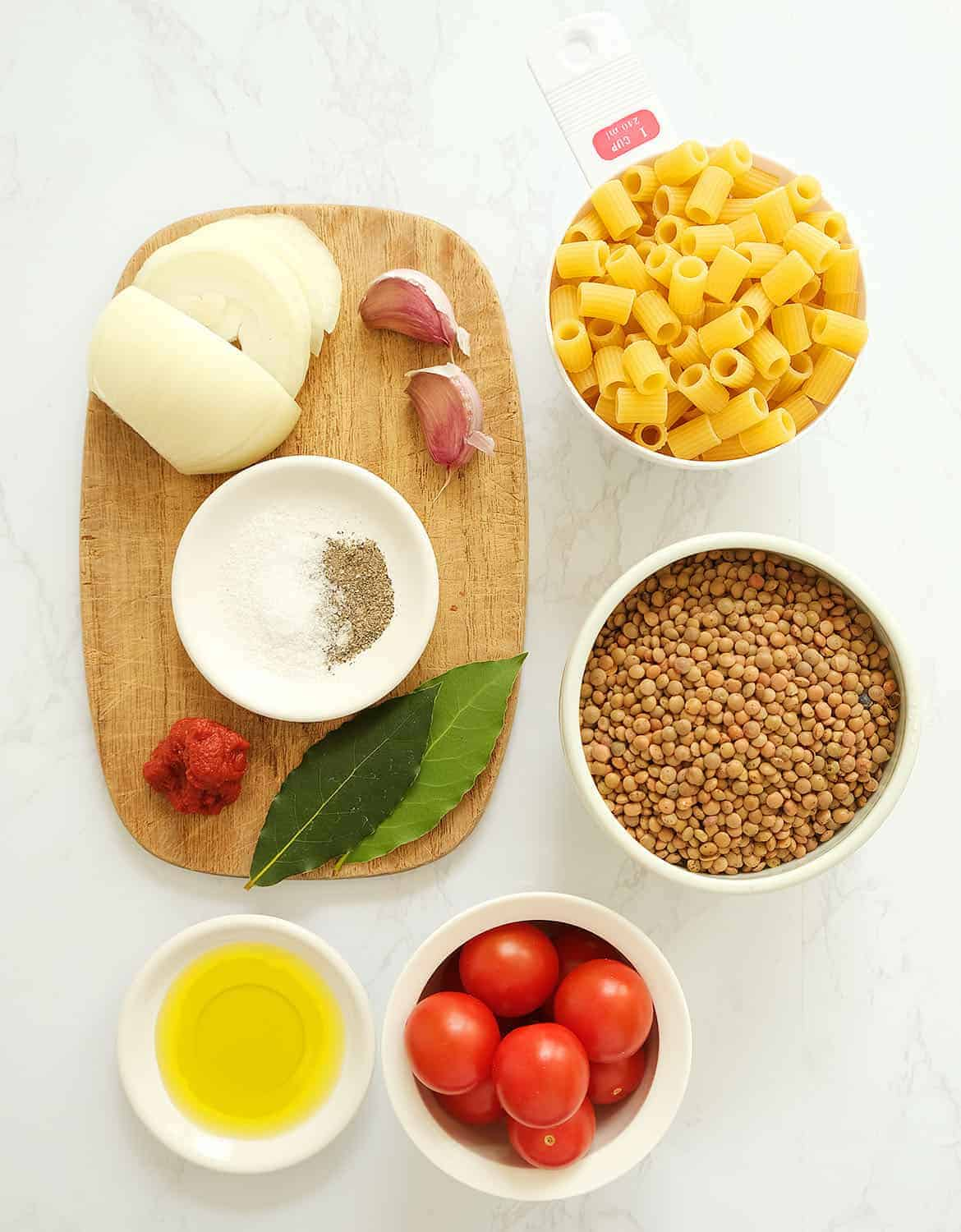 The ingredients for this pasta with lentils are arranged on a white marble table and a small wooden board.
