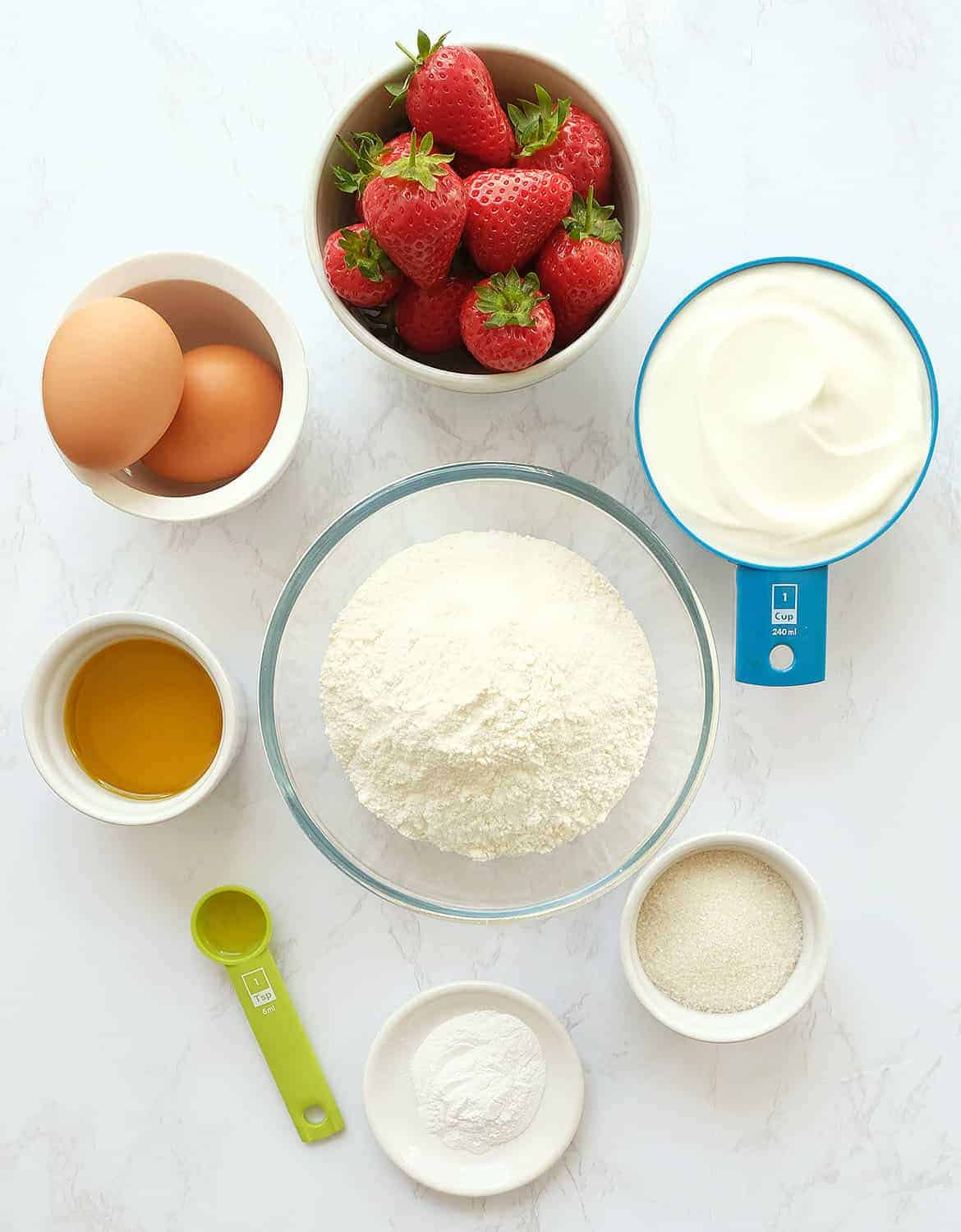 The ingredients for this strawberry bread are arranged on a white marble surface.
