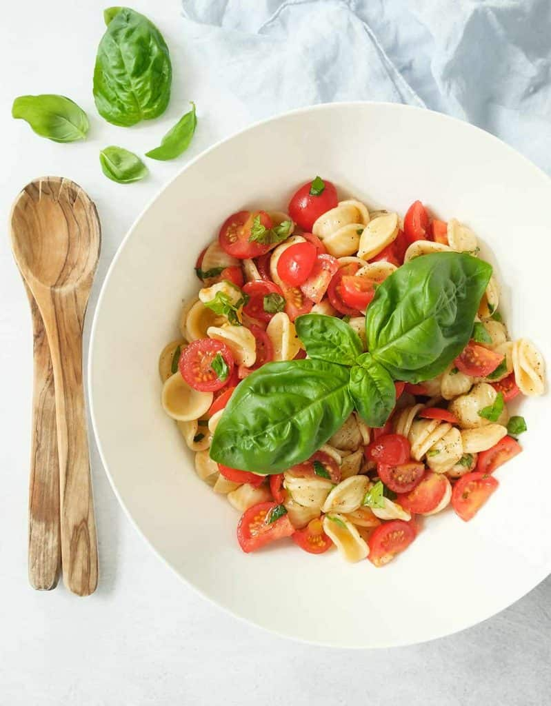 Tomato pasta salad with large basil leaves in a white salad bowl.