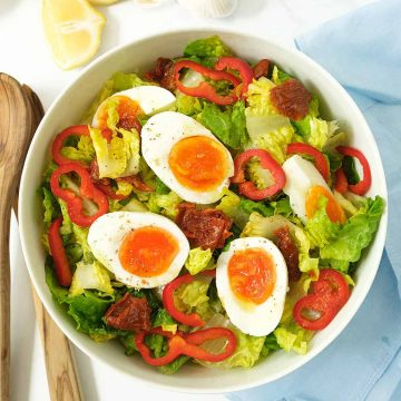 Lettuce and egg salad with sun dried tomatoes in a large white bowl.