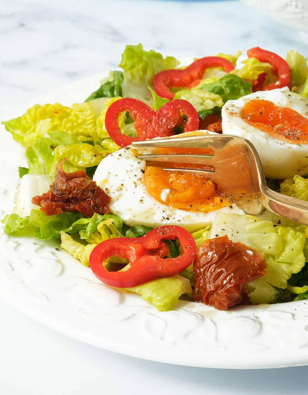 A fork breaking a soft boiled egg on a white plate full of lettuce salad.