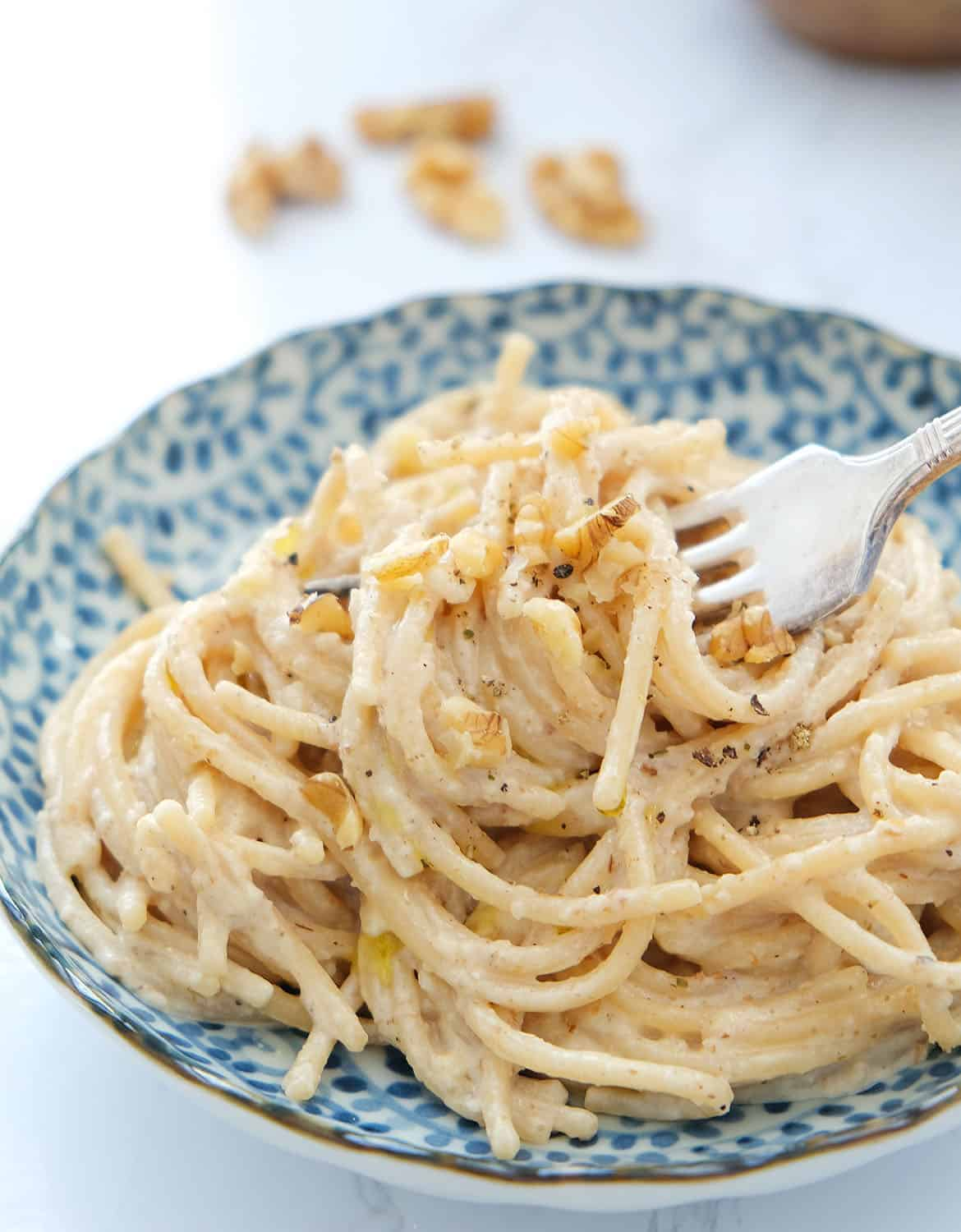 Easy spaghetti with walnut sauce and chopped walnuts in a blue bowl with a fork.