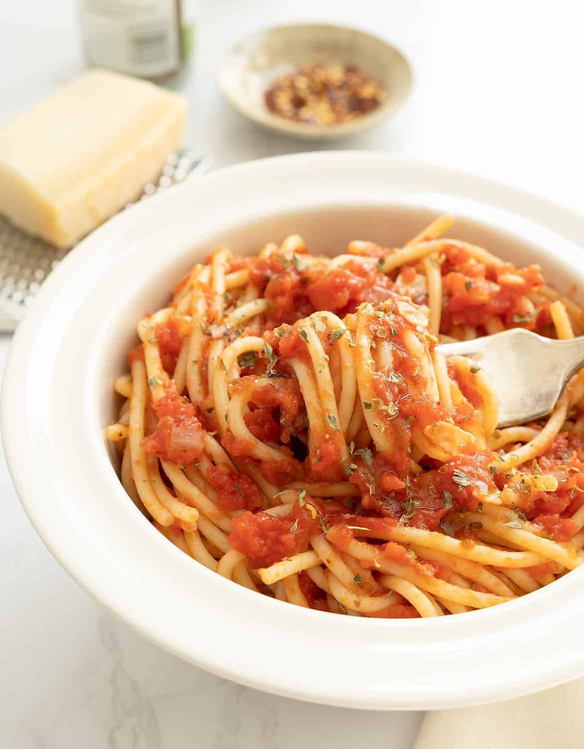 Quick spaghetti marinara in a white bowl with a fork.
