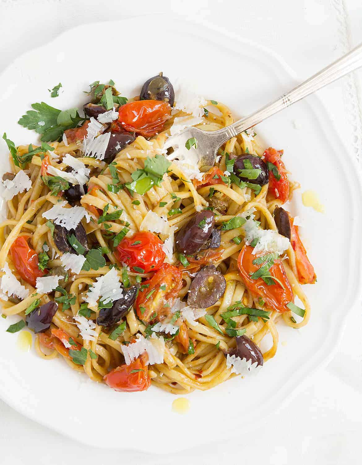 Quick pasta recipe with olives, tomatoes, parsley leaves on a white plate.