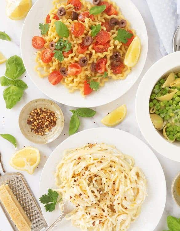 Three white plates with different quick pasta recipes over a white table.