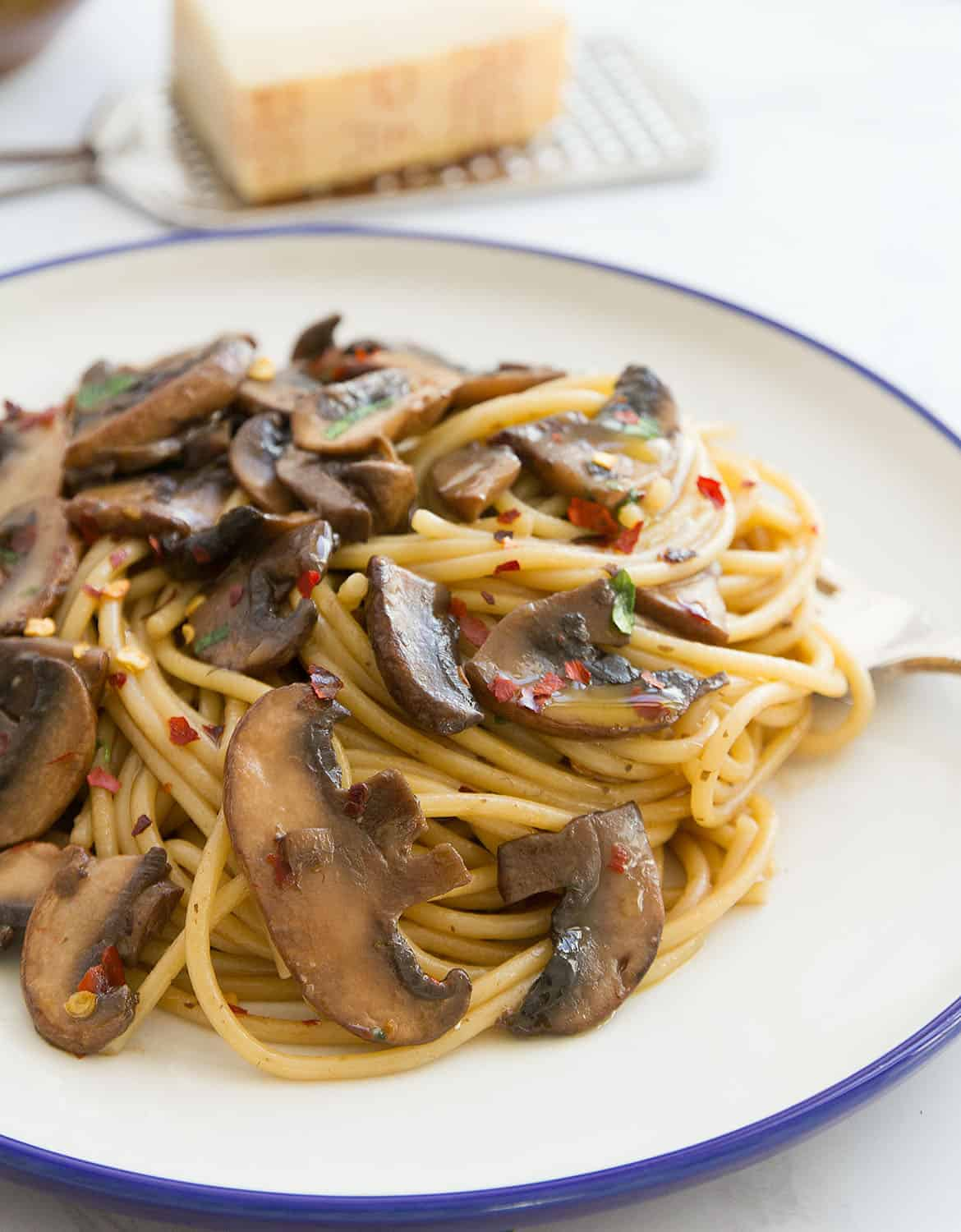 Quick mushroom spaghetti on a blue rimmed white plate.