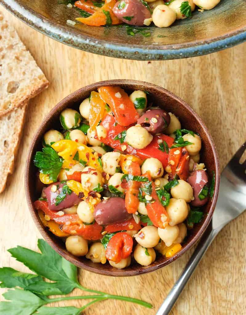 Chickpea salad in a wooden bowl over a wooden board.