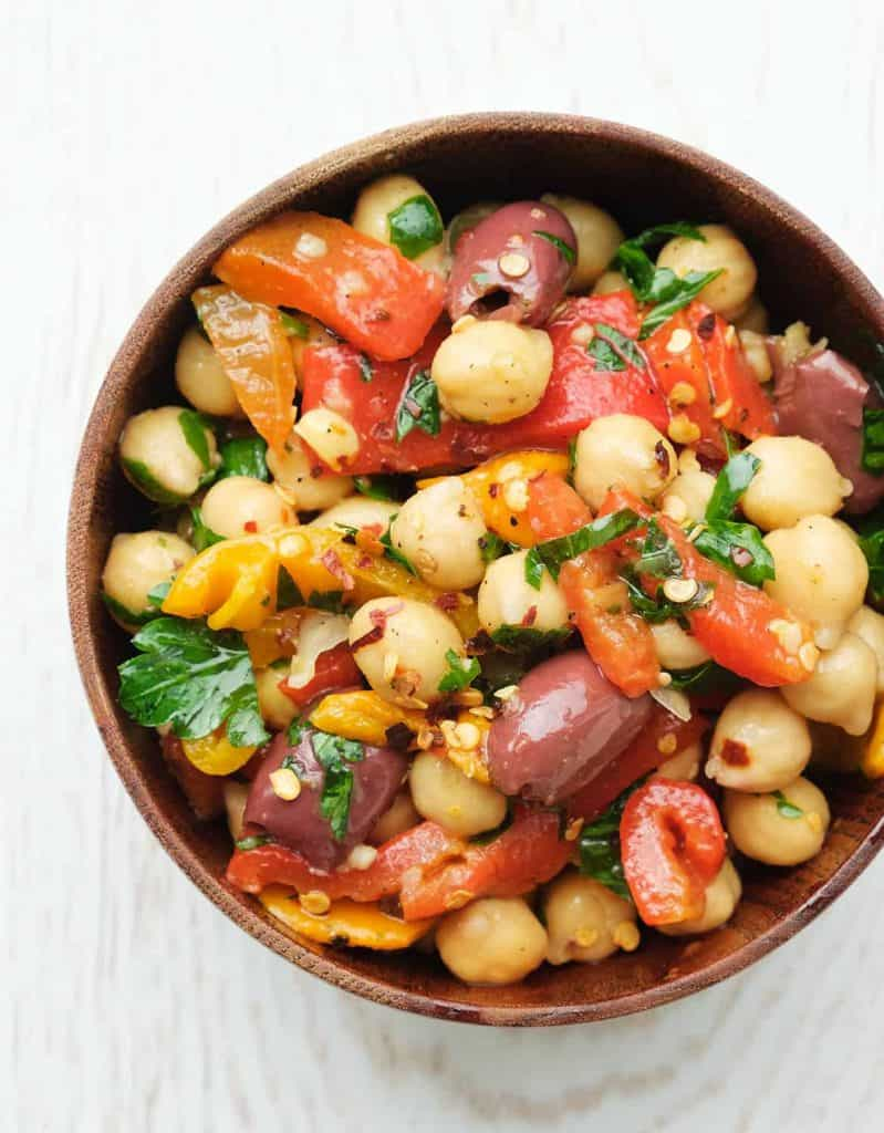 Spicy chickpea salad in a wooden bowl over a white background.