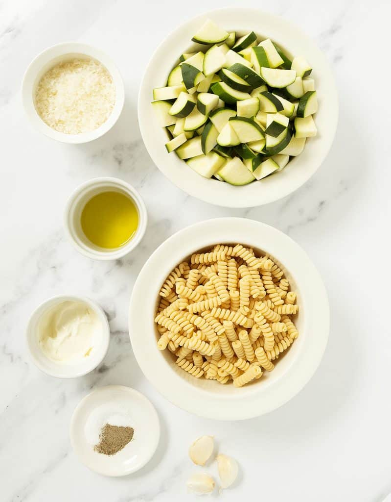 The ingredients for this pasta with zucchini recipe are arranged over a white marble background.