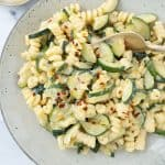 Creamy pasta with zucchini with red chili flakes on a grey plate.