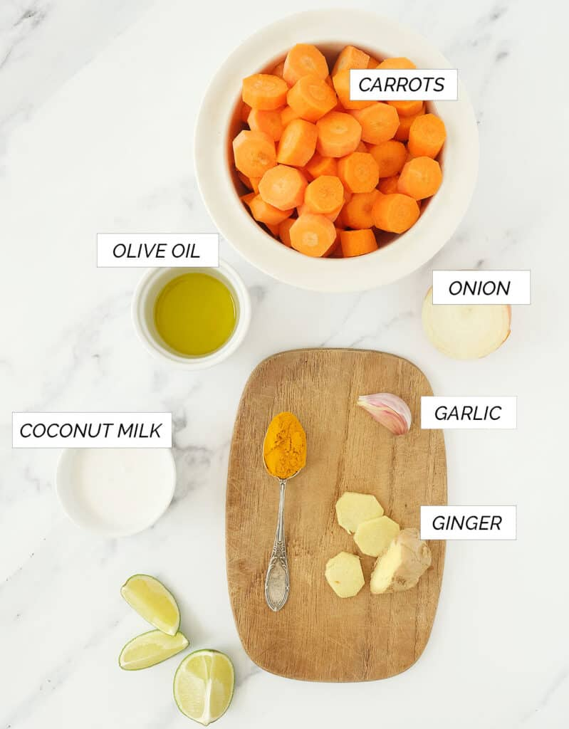 Top view of the ingredients to make this carrot ginger soup over a white background.