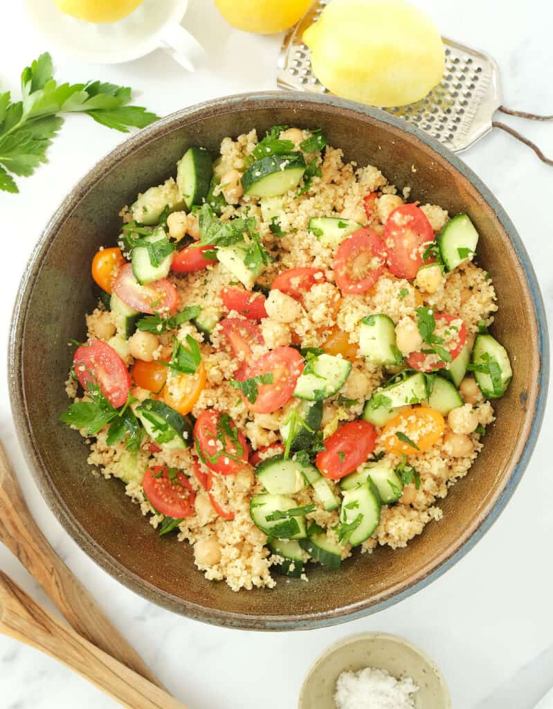The lemon couscous salad with cherry tomatoes and cucumber in a large brown salad bowl.