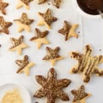 Top view of orange cookie stars dipped in chocolate.