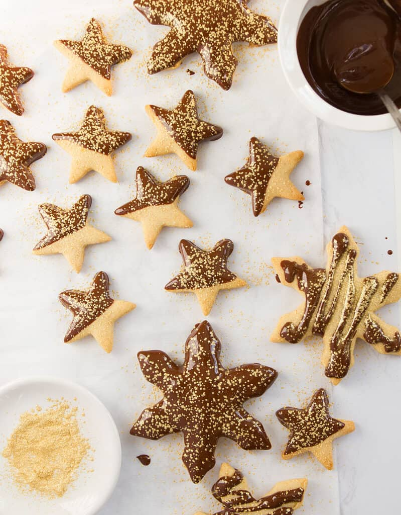 Top view of orange cookies stars dipped in dark chocolate and sprinkled with golden dust.