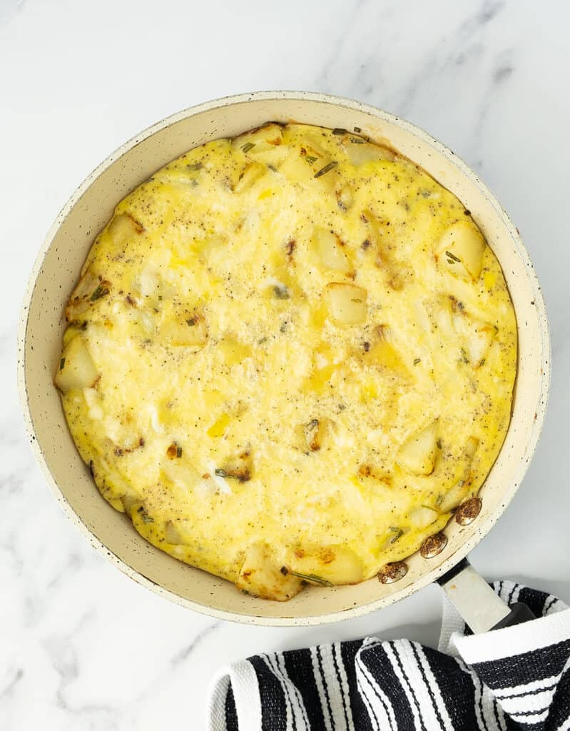 Top view of a round pan over a white background full with potato frittata.