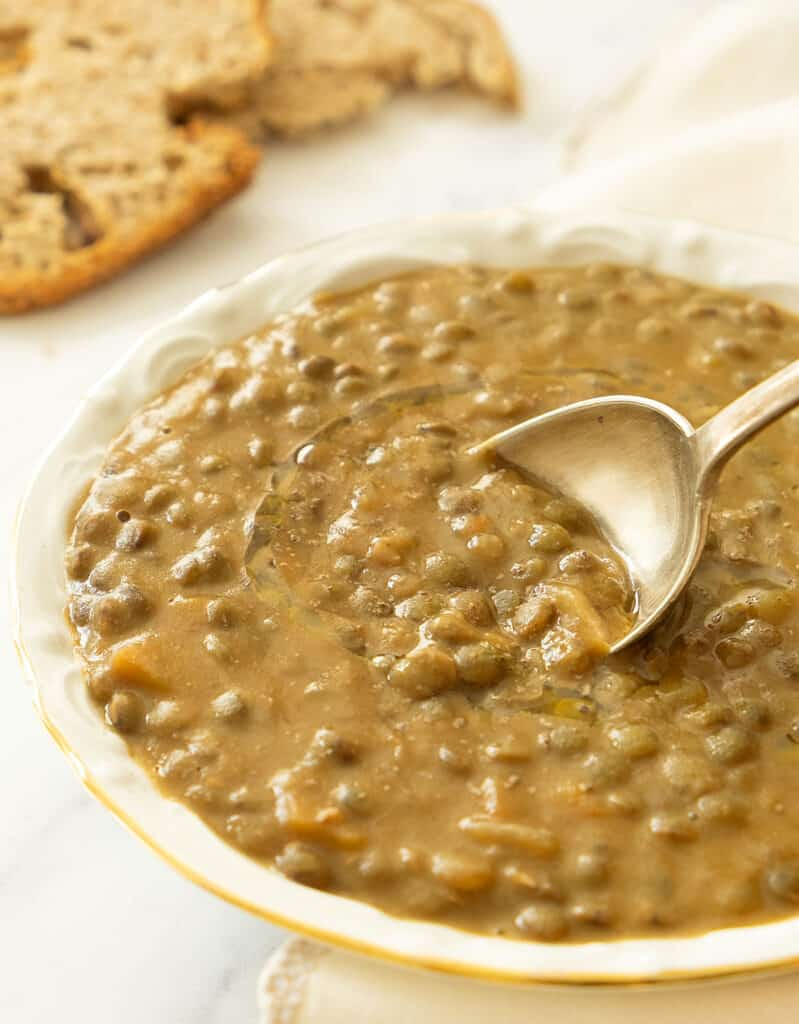 Close-up of a white bowl full of green lentil soup with a spoon, slices of bread in the background.