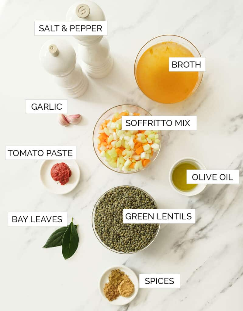 The ingredients for this green lentil soup are arranged over a white marble table.